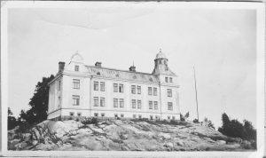 Mustavalkoinen valokuva, jossa kallion päällä iso rakennus.jossa