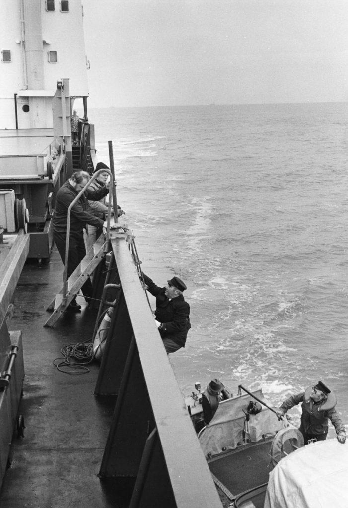 Mustavalkoinen kuva rahtilaivan laidalta. Mies kiipeämässä kylkeä pitkin alukseen. Alhaalla näkyy luotsikutteri ja sen kuski.