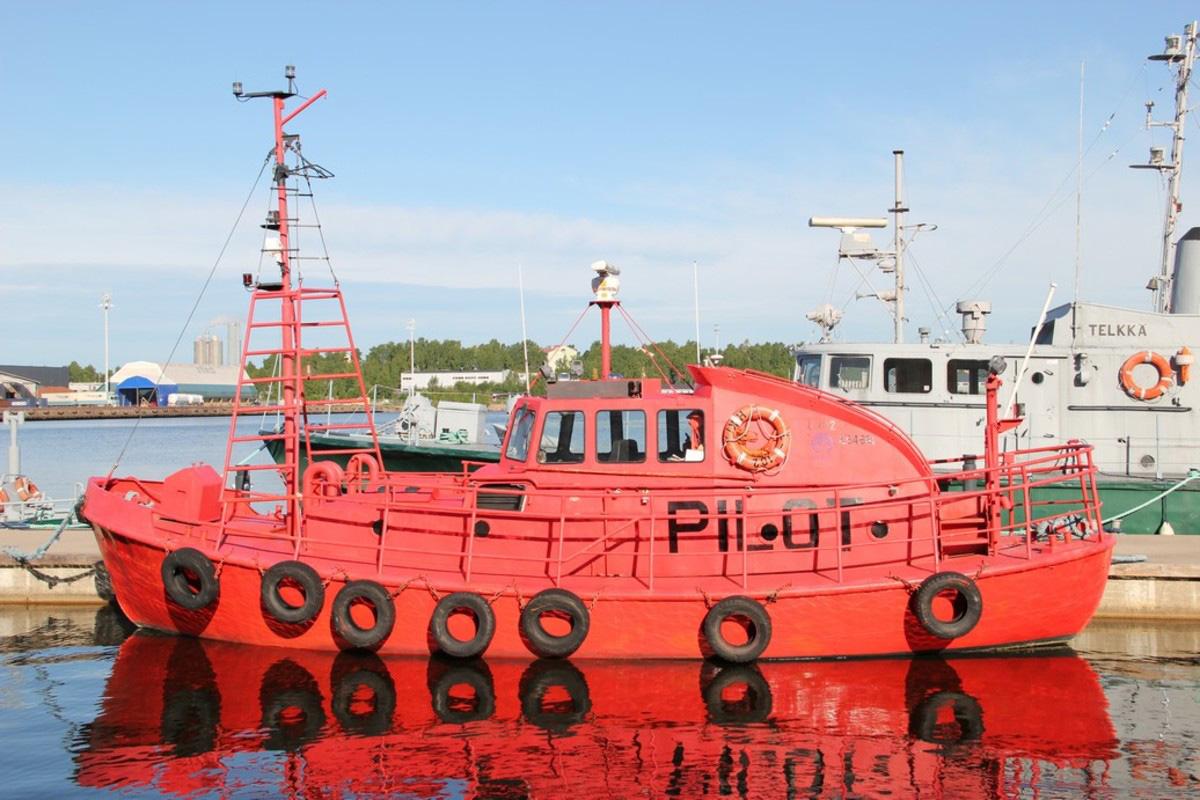 Oranssinpunainen vene laiturissa. Kyljillä autonrenkaat.