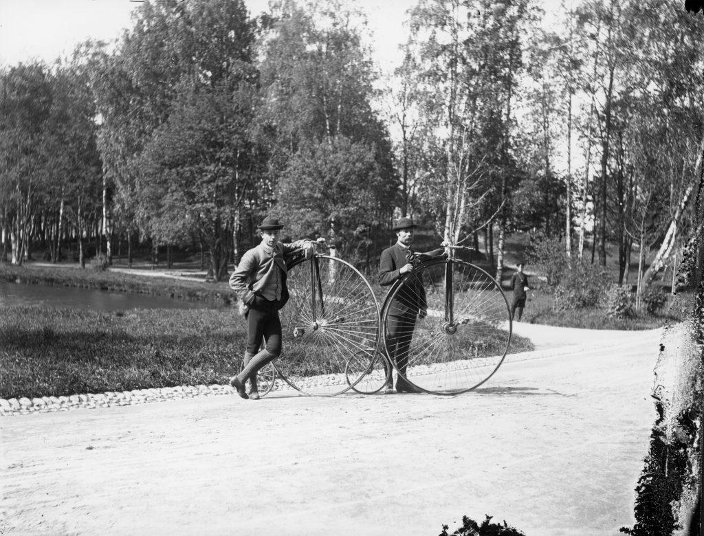Mustavalkokuvassa kaksi miespyöräilijää korkeapyöräisineen puistomaisemassa 1880-1890-lukujen Helsingissä.