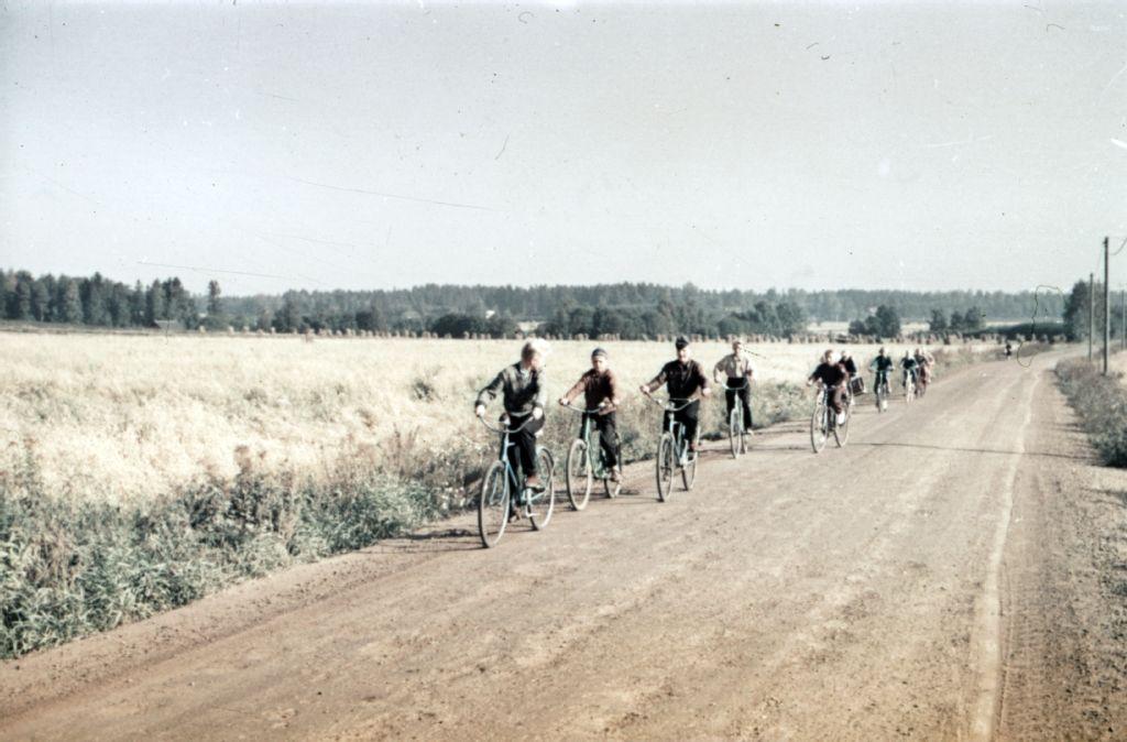 Nuoria pyöräilijöitä Helsingin maalaiskunnassa ajamassa pellon viertä kulkevaa maantietä.