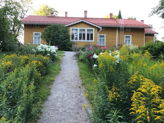 Keltainen puutalo, johon johtaa hiekkapolku puutarhassa kukkivien istutusten välissä.