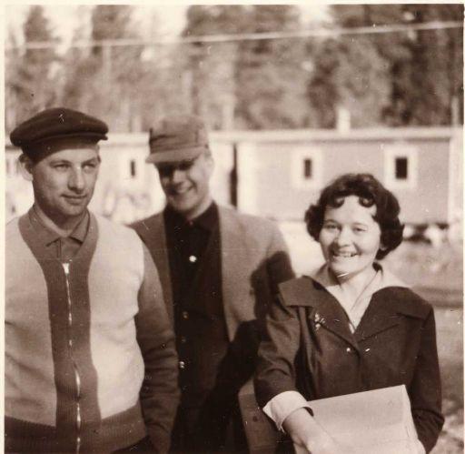 Kaksi miestä ja yksi nainen siirtotyömaa parakkien edessä hymyilemässä kameralle.