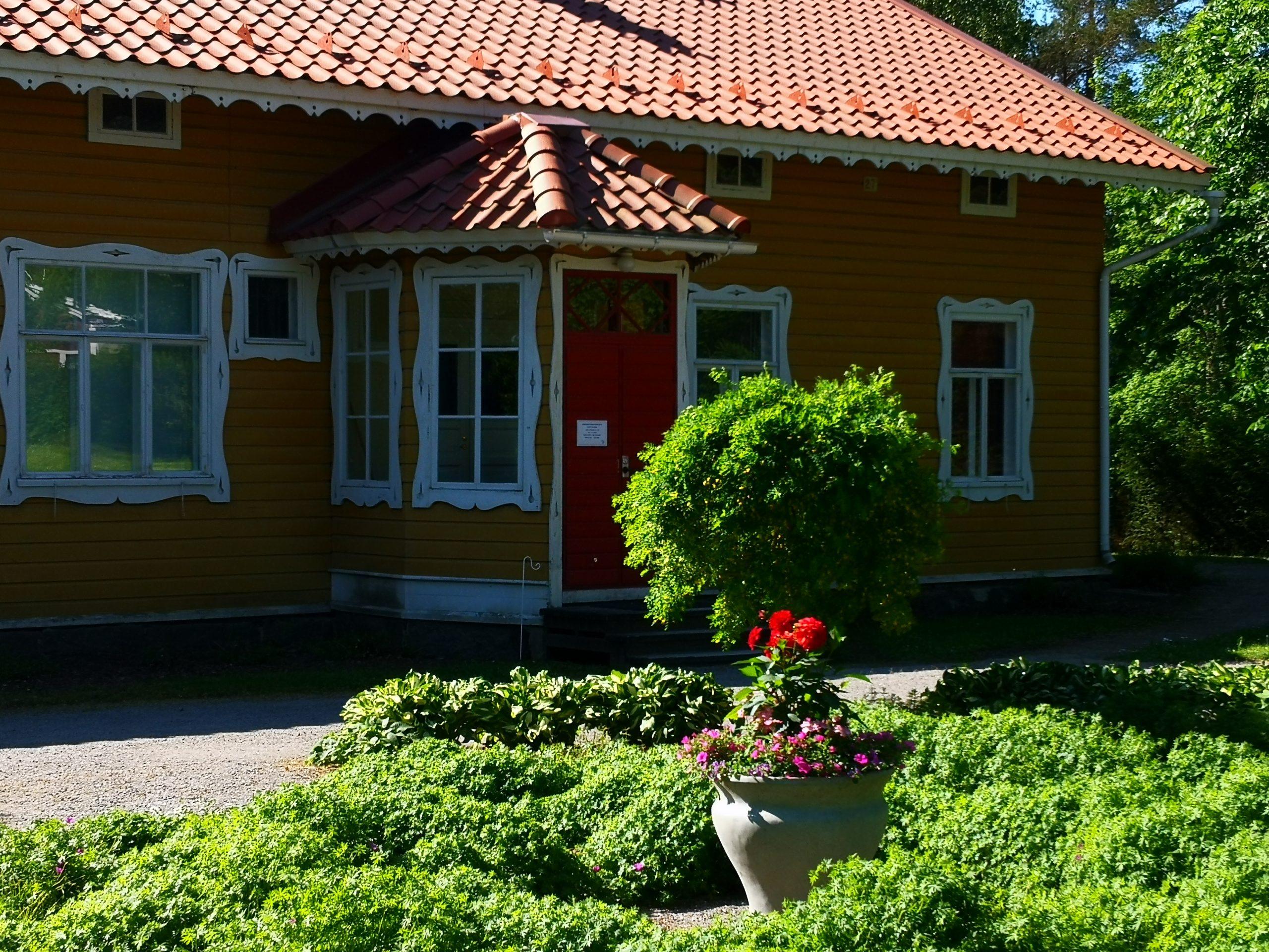 Vanha keltainen puurakennus punaisine kattoineen. Ulkoneva kuisti ja kauniisti muotoiltu etupuutarha.