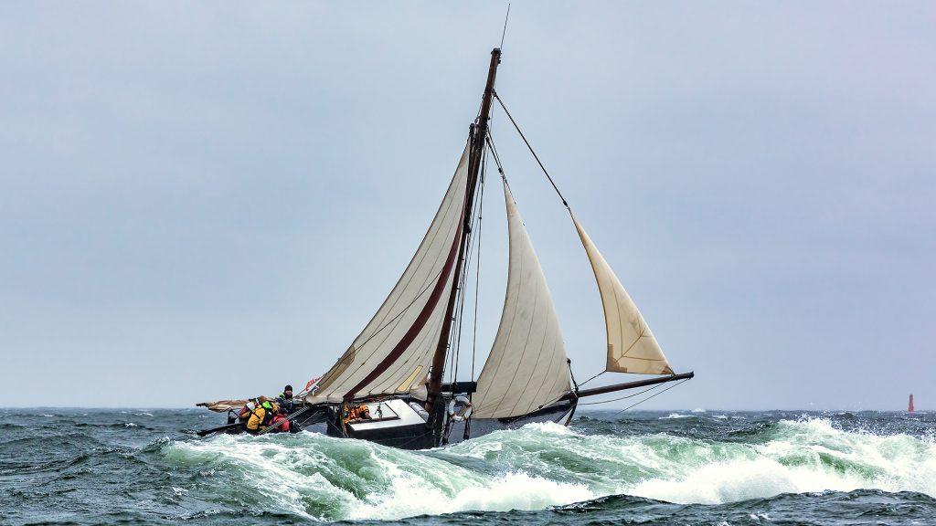 Kovalla tuulella purjehtiva vene. Kallellaan. Etualalla isoja vaahtopäisiä aaltoja.