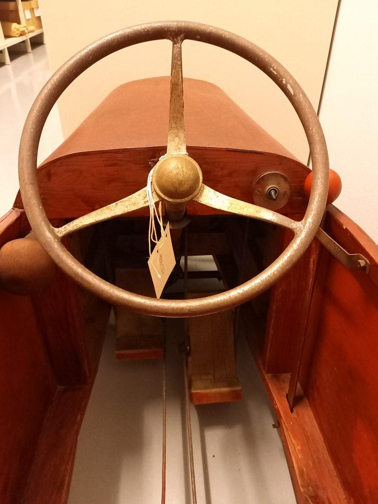 Punaruskea polkuauto 1940-luvulta, jossa on iso ratti ja puiset polkimet.
