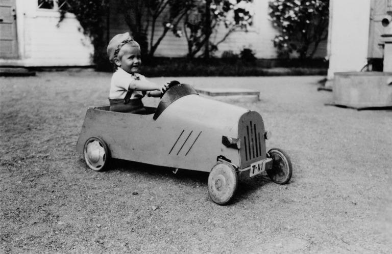 1950-luvun mustavalkokuvassa pienipoika ajaa hymyillen polkuautolla, jossa vaneri on taivutettu kauniin pyöreille muodoille.