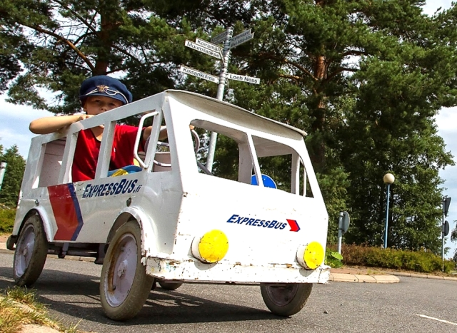ExpressBus-väreihin maalattu polkuauto, jossa pieni hattupäinen poika.