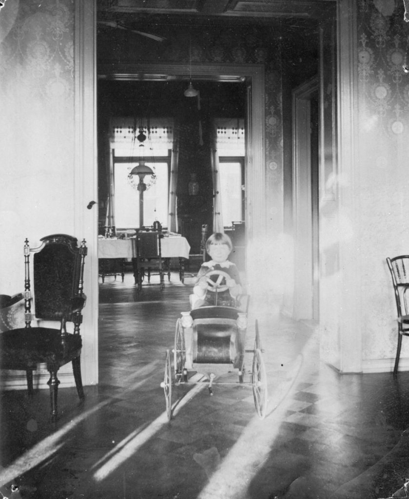 Ylivaloittuneessa vanhassa mustavalkokuvassa näkyy lapsi ajamassa kartanon salissa polkuautolla, jossa on 1890-luvun autolle tyypilliseen tapaan kapeat renkaat ja käynnistyskampi.