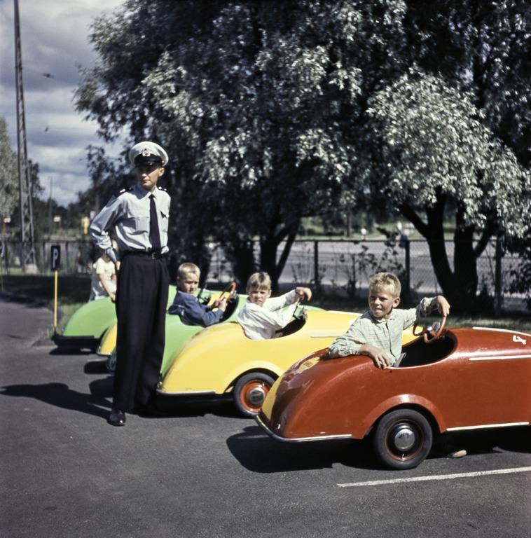 Poliisi tyylikkässä uniformussa valkoisen koppalakin kanssa lasten liikennepuistossa. Vieressä lapsia punaisessa, keltaisessa ja vihreässä virtaviivaisessa polkuautossa odottamassa omaa vuoroaan parkkiruudussa.