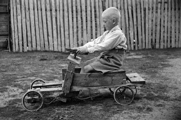 Mustavalkokuvassa pieni vaaleapäinen poika istuu laudoista kootussa autossa.