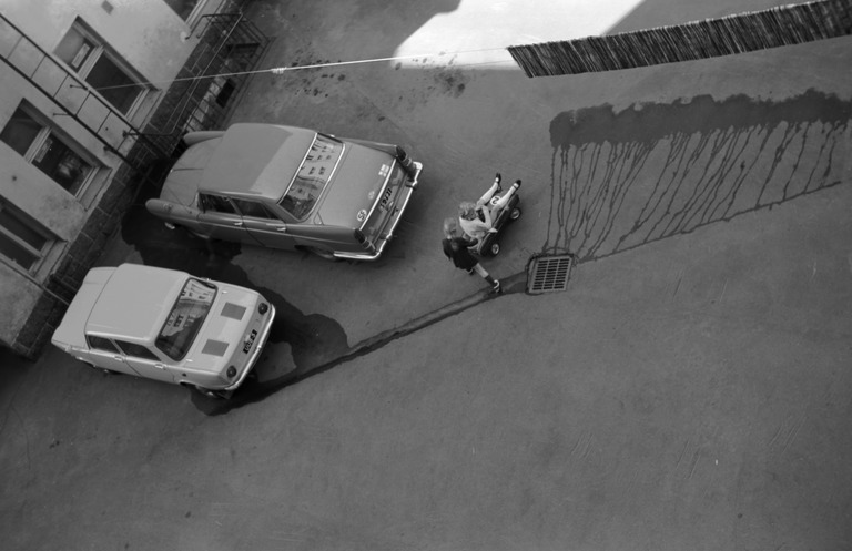 Kerrostalon asfaltoidulla pihalla parkissa kaksi henkilöautoa. Pihalla valuttaa vettä asfaltille narulle kuivamaan ripustettu räsymatto. Kaksi tyttöä leikkii näiden keskellä polkautossa.
