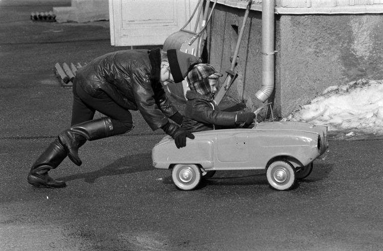 Mustavalkokuvassa 70-luvulta pipopäinen isompi poika työntää pienempää poikaa polkuautossa keväisellä asfalttipihalla.