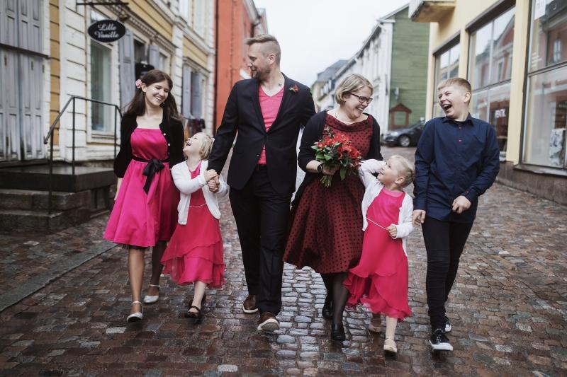 Juhla-asuinen perhe, isä, äiti ja neljä eri-ikäistä lasta, kävelevät kohti kuvaajaa ja hassuttelevat keskenään kävelykadulla.