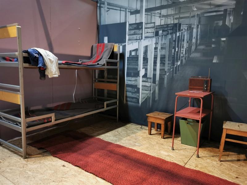 Mustavalkoinen suurkuva isosta asuntoparakista kerrossänkyrivistöineen takaseinällä. Sen edessä kerrossänky sekä yksinkertainen pöytä ja tuoli.
