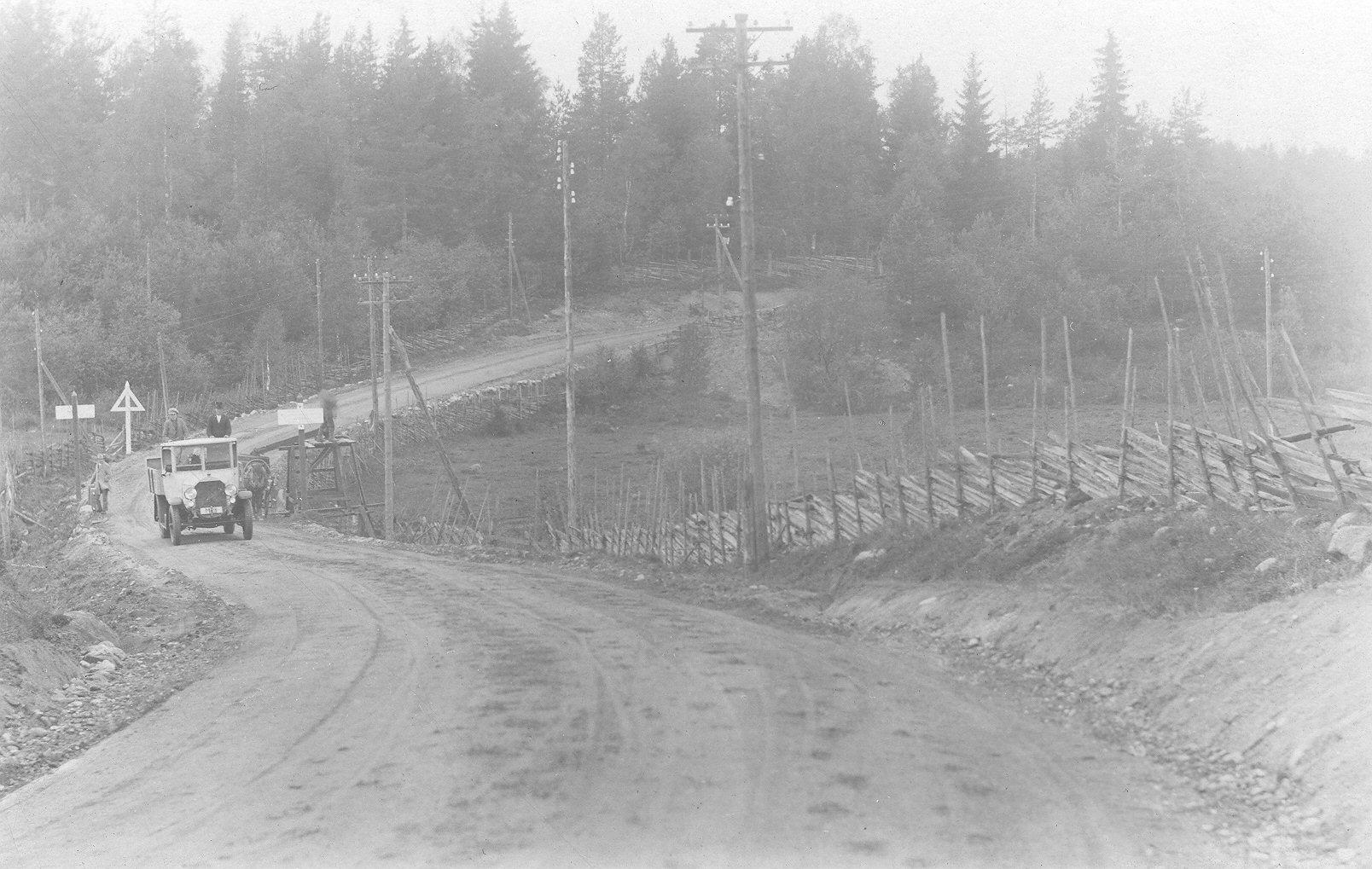 Mustavalkoisessa kuvassa 1920-luvun kuorma-auto ajaa mutkaista soratietä. Tien varressa on valkoisista laudoista tehty kolmionmallinen liikennemerkki.