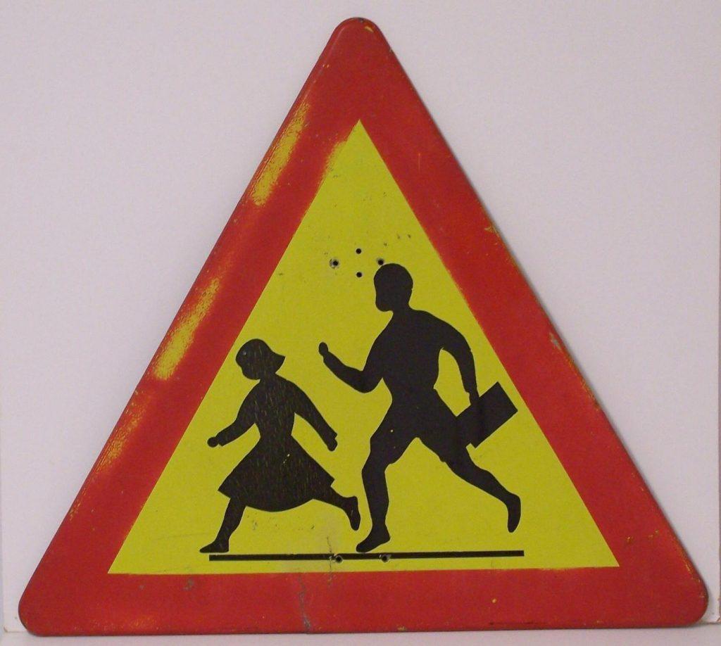 Kolmioliikennemerkki, jonka reunat ovat punaiset ja keskellä olevassa keltaisessa osassa on vuoden 1957 tyyliin pukeutuneet koululaiset, poika laukkukädessä ja tyttö hameessa.