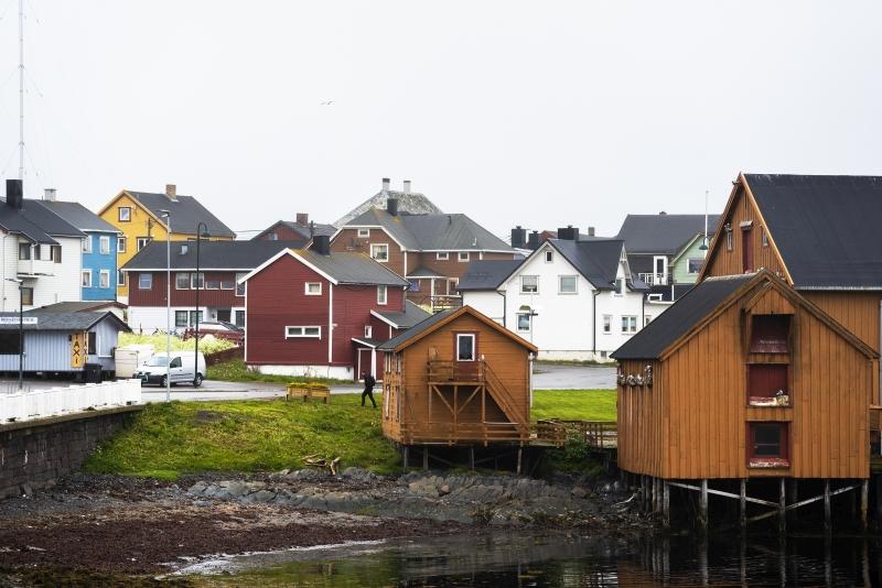 Erivärisiä rannikkokaupungin harjakattoisia taloja sommiteltuna kuvaan niin, että talot vievät kuvasta kaksi kolmasosaa ja taivaalle jää kolmas osa.