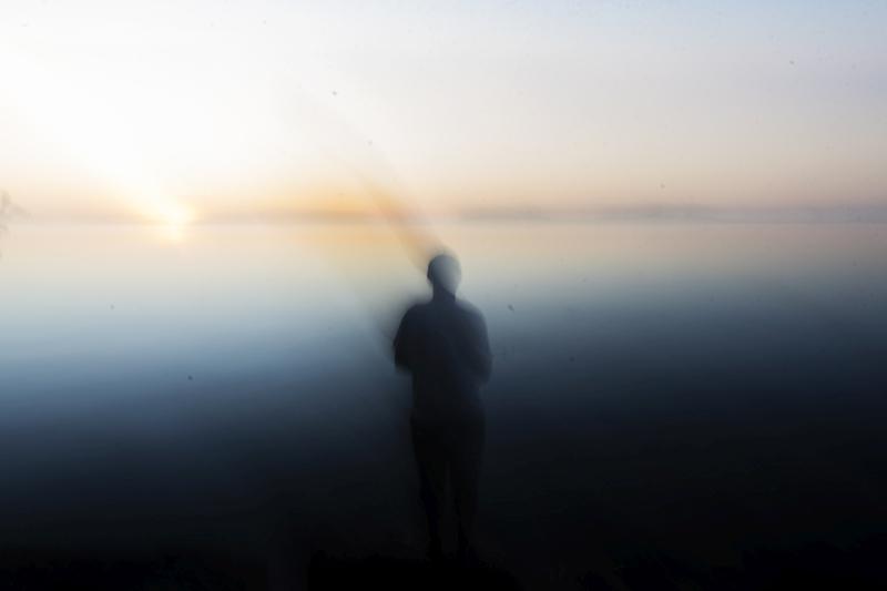 Vastavaloon järvenselkää vasten kuvattu henkilöhahmo näkyy vain etäisenä, tummana siluettina.