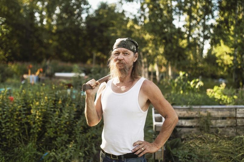 Valkoisessa hiattomassa paidassa, huivi päässään oleva partainen mies kirveenvarsi olallaan on kuvattu puolivartalokuvaan niin, että lantio ja vyö näkyy, mutta ei jalkoja. Taustalla puutarhan kasvimaita ja komposti.