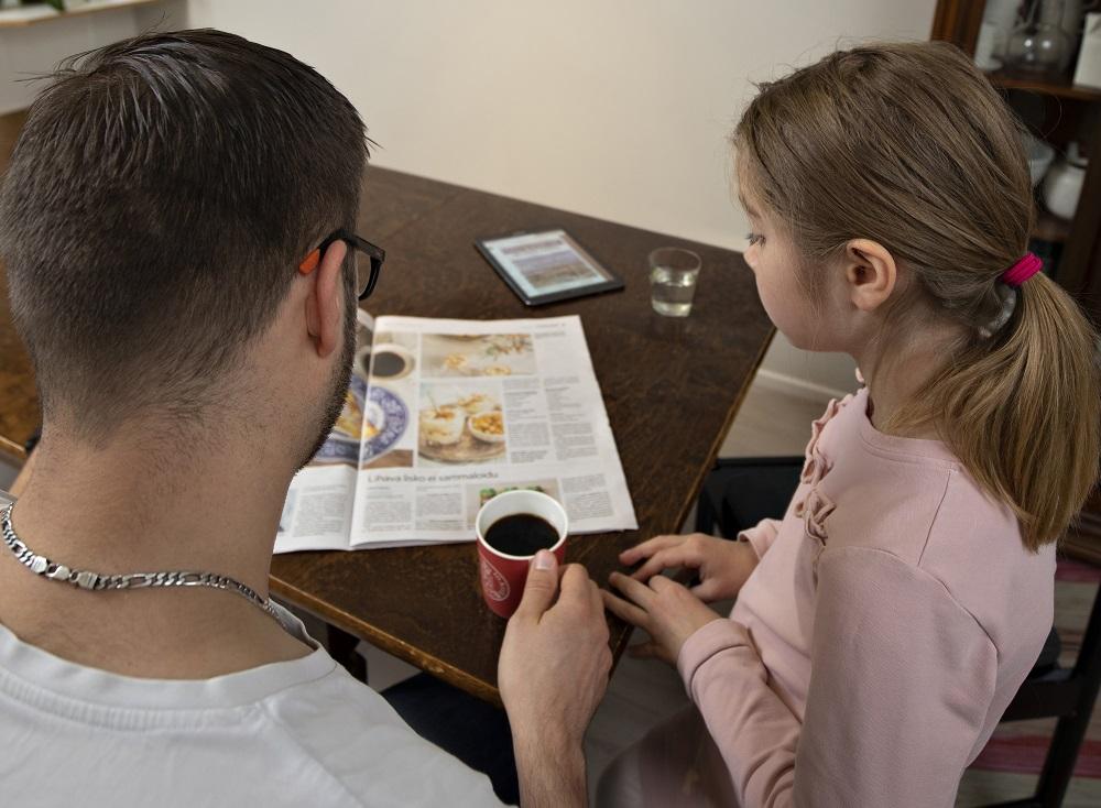 Perhe aamukahvipöydässä sanomalehden äärellä