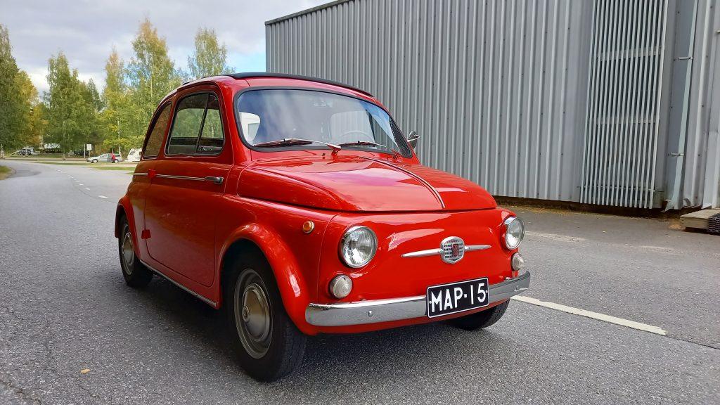 Paloautonpunainen, pieni Fiat 500 kuvattuna asfalttitiellä harmaata seinää vasten.