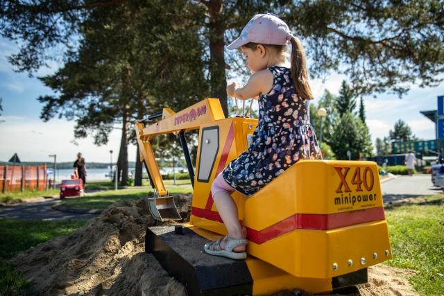Ranta-alueella keltainen minikaivuri, jonka päällä kesämekkoon ja lippalakkiin pukeutunut tyttö ohjaa kaivuria kaivamaan hiekkakasaa.